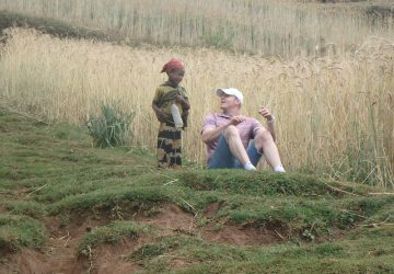 a man sitting in a field talking to a child
