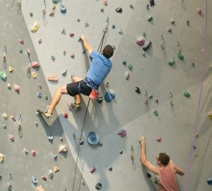 a couple climbing a wall