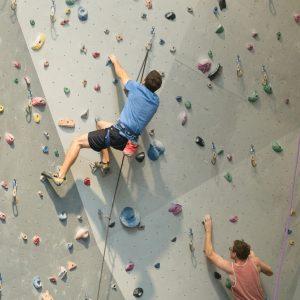 a couple climbing a wall