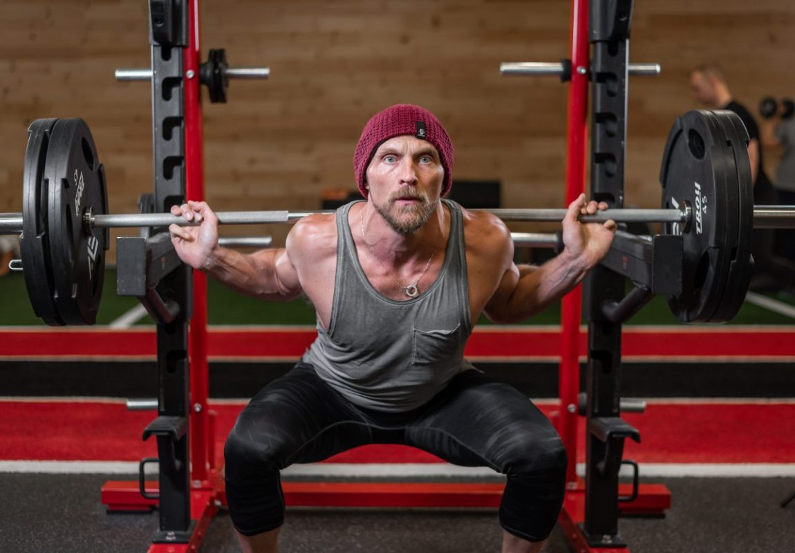 man doing squats in the gym