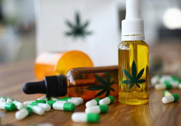 Close-up of medical marijuana products with capsules and cannabinoid oil in bottle with marihuana leaf on it. Pain medication for treatment. Medicine and healthcare concept