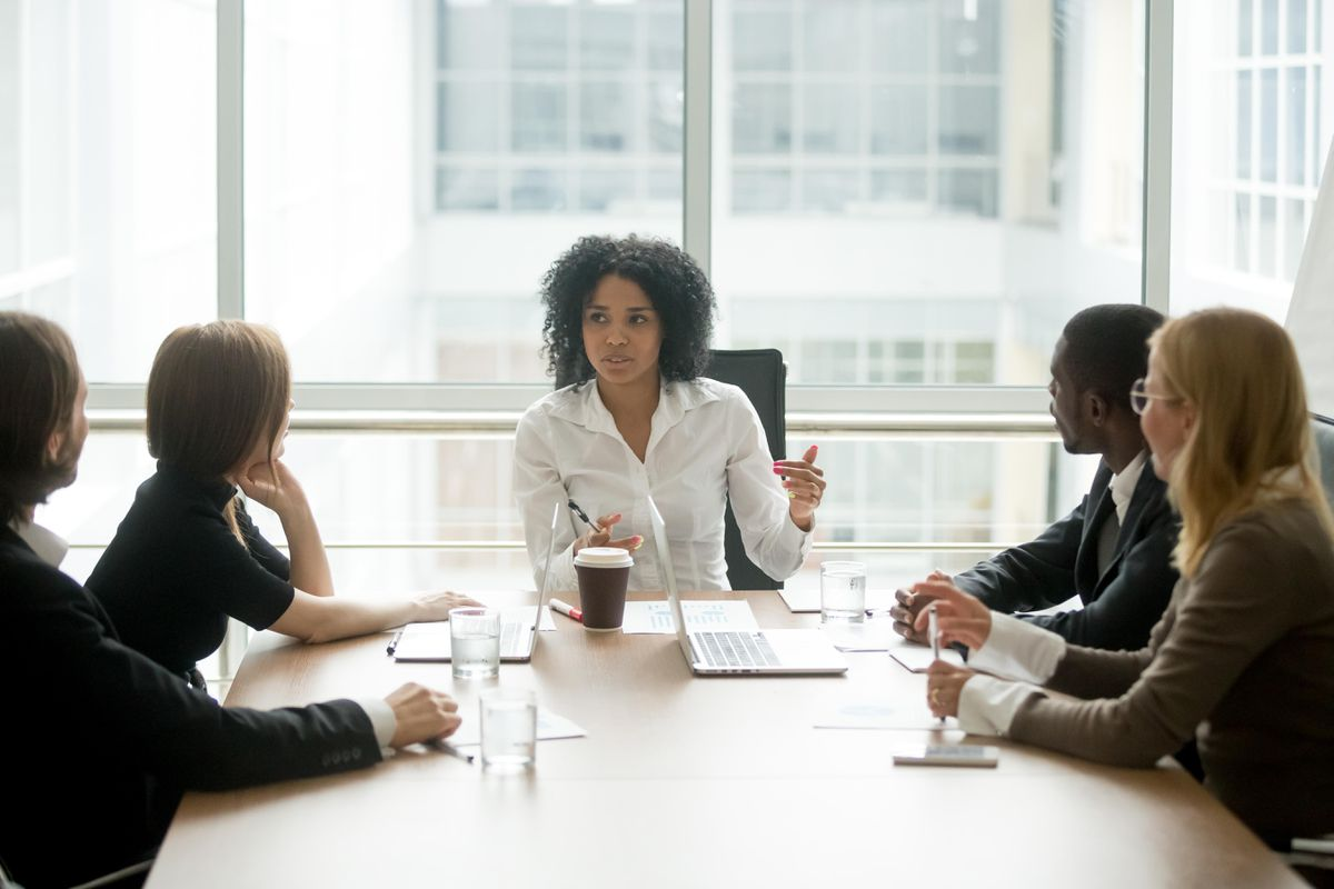 a woman leading a group meeting
