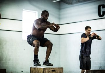 a pair of men doing box jumps