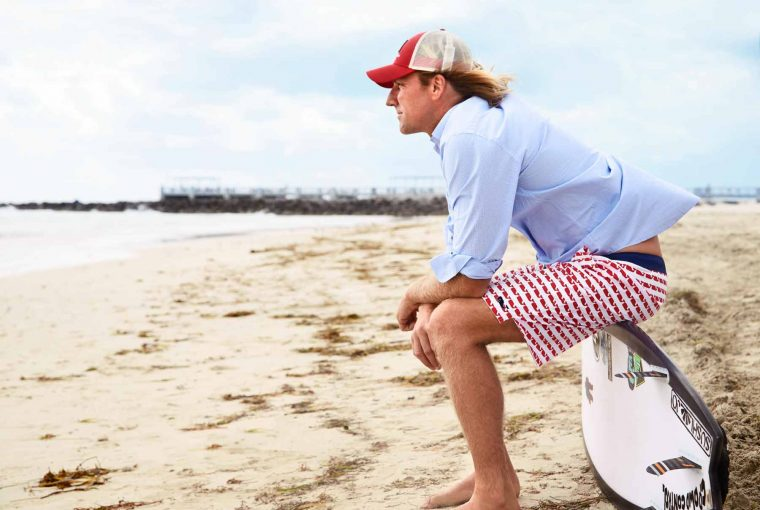 a man sitting on the beach with a surf board